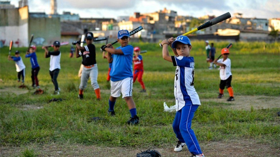 Cuban children practice baseball in a field of Havana