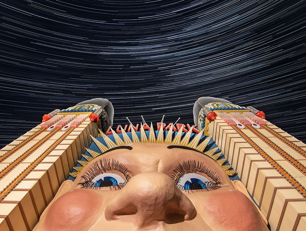 An image showing a park entrance featuring a large face with stars in the sky above