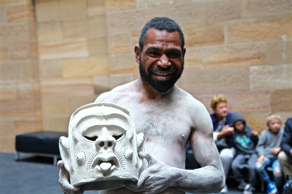Kori, one of the four 'mud men' in Sydney for the exhibition, smiles as he holds a clay mask