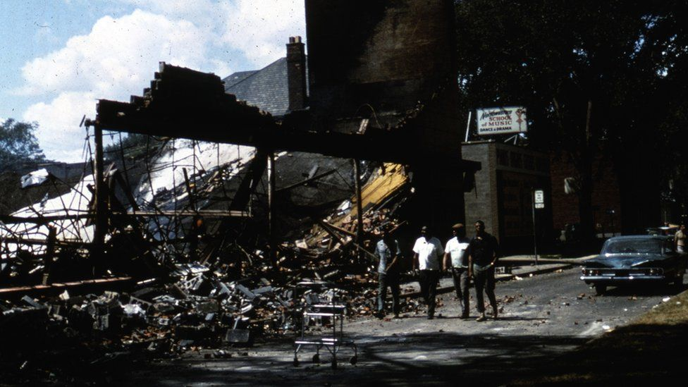 Four unidentified African American men walk past the rubble of a storefront in Detroit 1967.