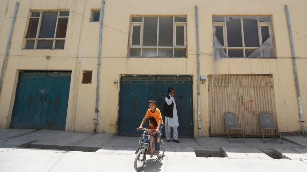 An Afghan boy rides his bicycle in front of a house, where a German aid worker and an Afghan guard were killed last night, in Kabul, Afghanistan May, 2017