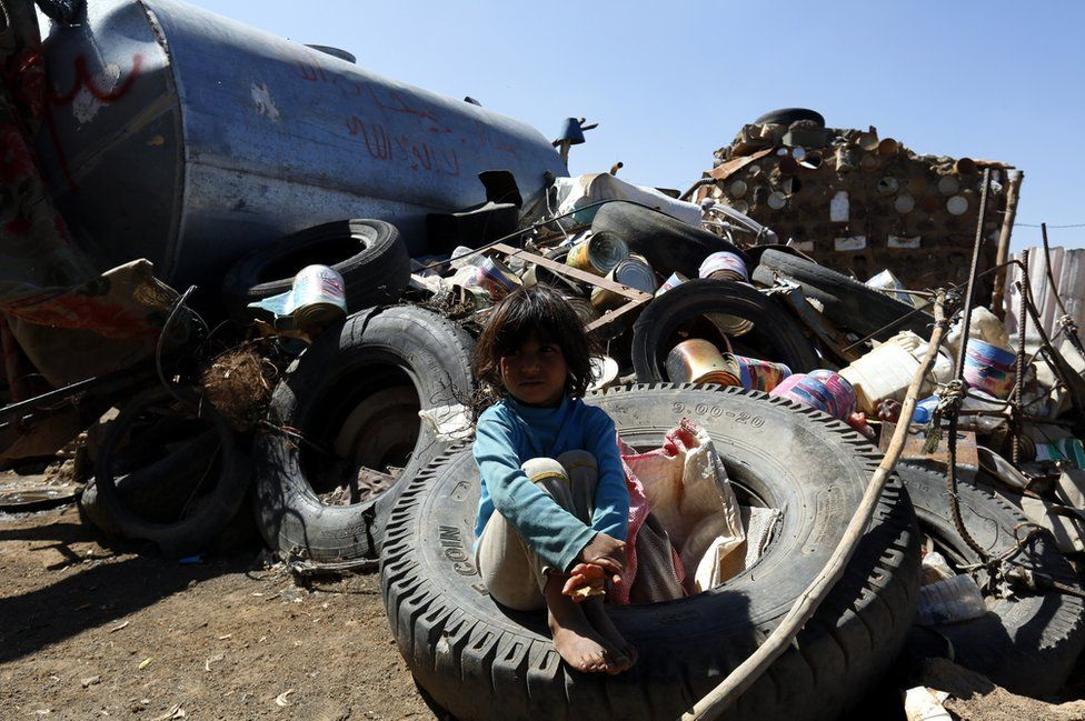 A small child sits on a scrapheap