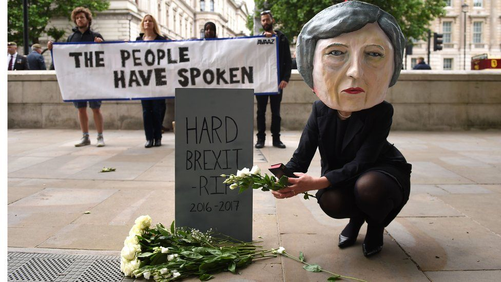 A life-size giant-headed puppet of Theresa May leaving flowers at a tombstone bearing the words Hard Brexit RIP