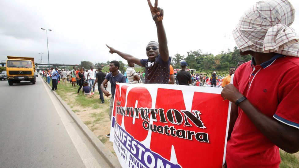 Members and supporters of the Ivorian Popular Front (FPI) party hold a banner as they protest against President Alassane Ouattara's new constitution, in Abidjan on 8 October