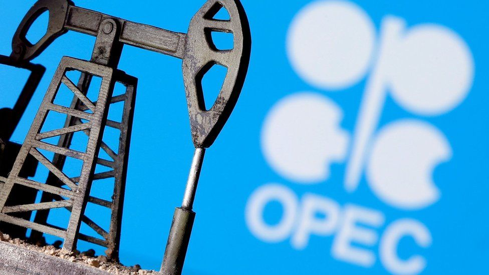 A 3D-printed oil pump jack is seen in front of the Opec logo (14 April 2020)