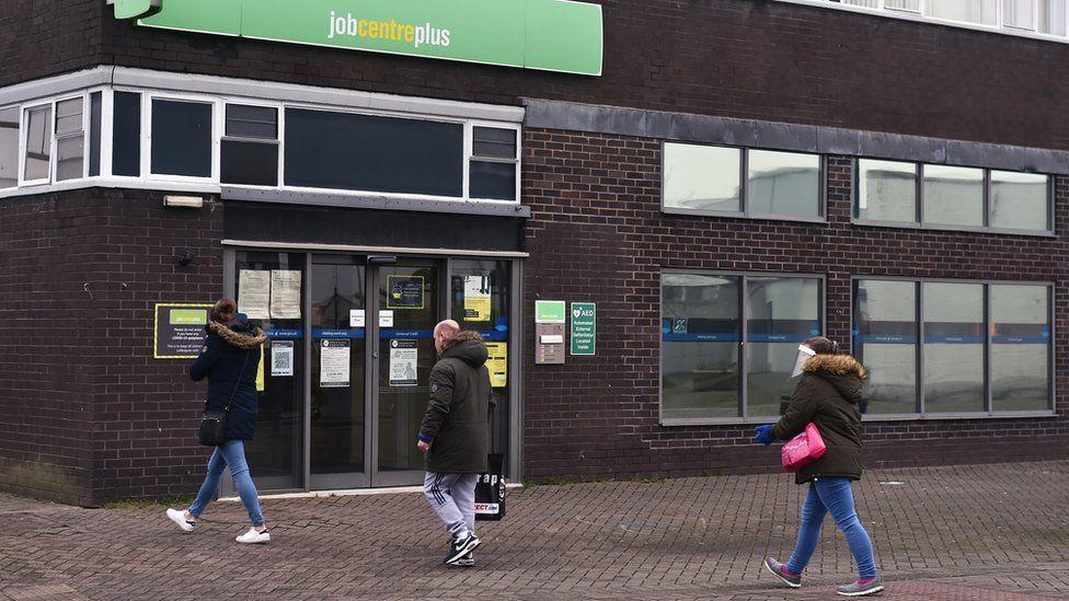 People walk past a Job Centre office
