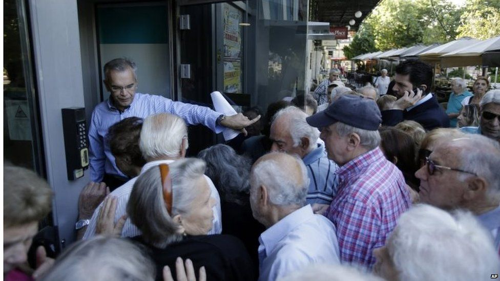 A manager of a bank opens the entrance for the pensioners in Athens, Wednesday, July 1, 2015
