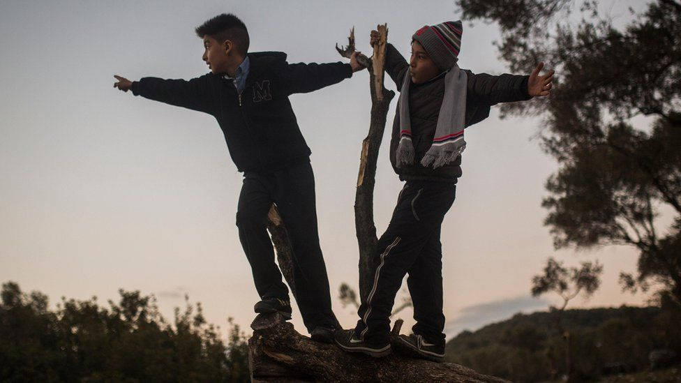 Two boys play on a tree outside a migrant registration centre in Moria, on Lesbos (26 December)