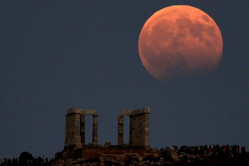 Temple of Poseidon is seen as a full moon is partially covered by the Earth's shadow during a lunar eclipse in Cape Sounion, east of Athens, Greece, August 7, 2017
