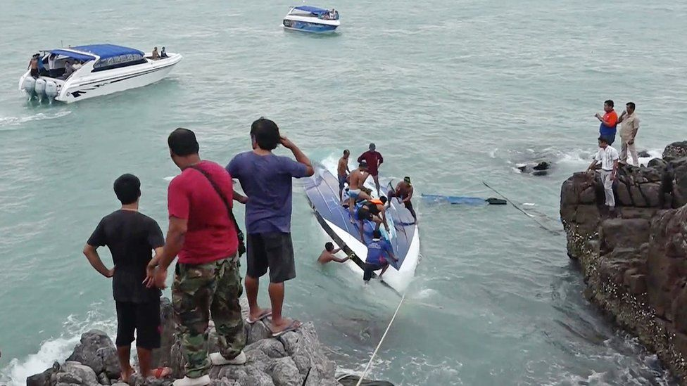 A capsized boat and rescue workers