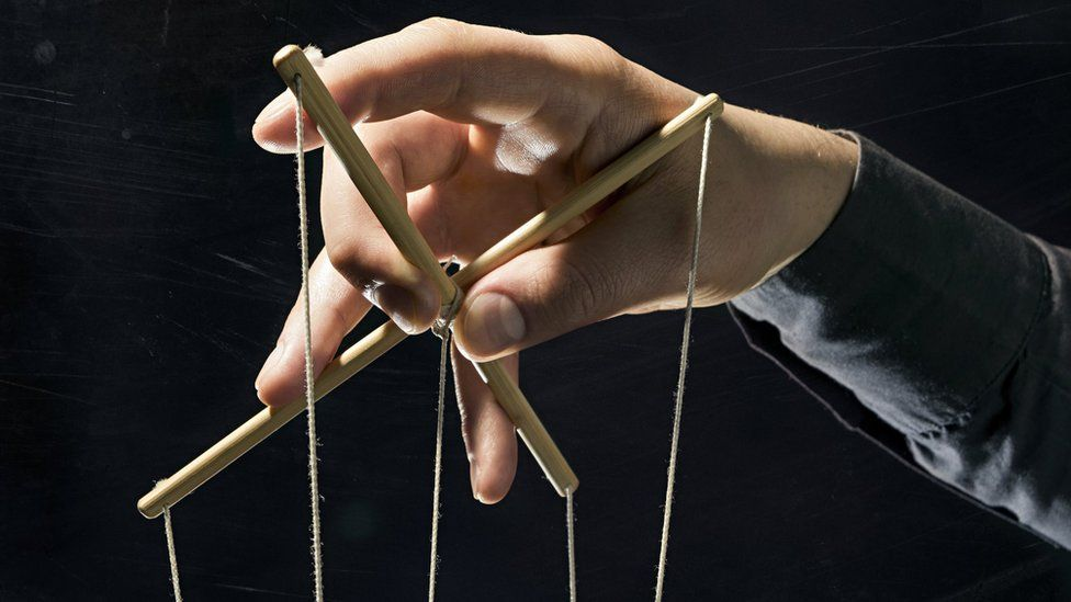 A puppet's controls with a man's hands holding it