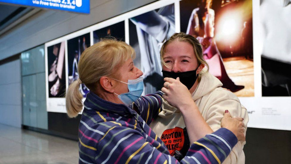 Relatives embrace as they arrive from the United States at Heathrow's Terminal 5