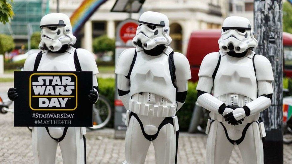 Three people dressed as Star Wars' stormtroopers hold a sign advertising Star Wars day