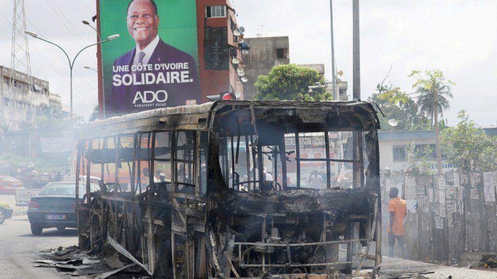 A campaign billboard of Ivory Coast President Alassane Ouattara seen behind a bus burned by protesters against his decision to stand for a third term, in Abidjan, Ivory Coast - 19 October 2020
