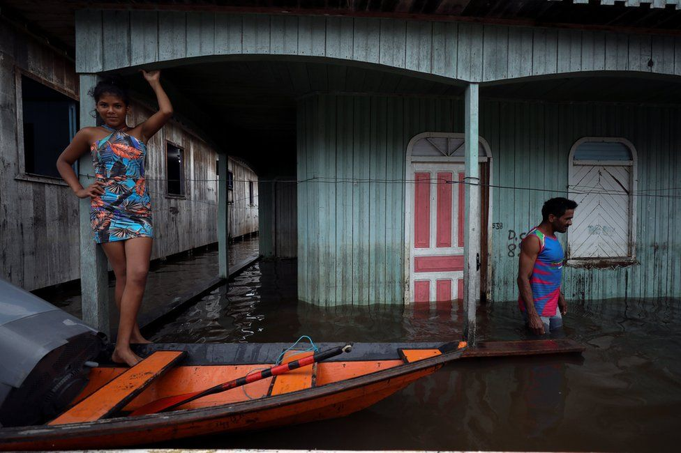 People are seen on a street flooded by the rising Solimoes river
