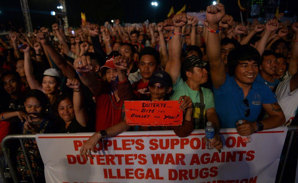 Supporters of President Rodrigo Duterte raise clenched fists during a rally at a park in Manila on February 25, 2017