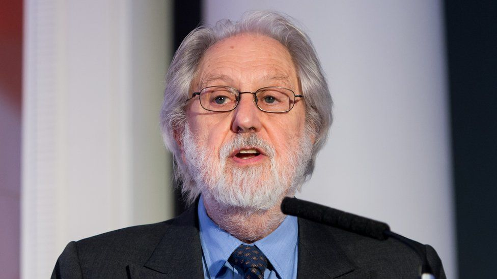 Lord Puttnam is seen speaking from a podium