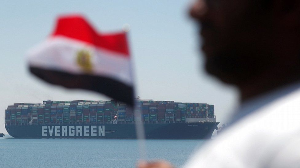 """A man holds an Egyptian flag as Ever Given is seen at the Suez Canal in Egypt""""s Great Bitter Lake in Ismailia, Egypt, July 7, 2021"""
