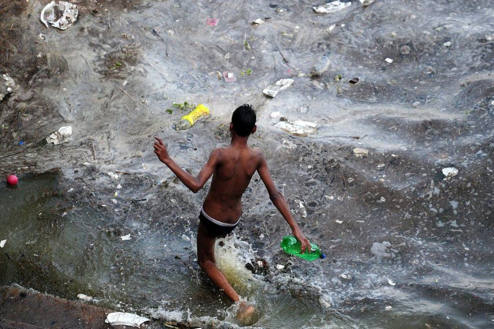 An Indian youth walks into polluted flood waters after the river Ganges rose following heavy monsoon rains in Allahabad on July 10, 2016.