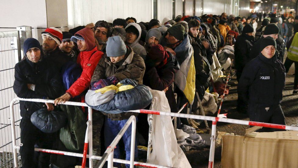 Migrants queue on a street to enter the compound outside the Berlin Office of Health and Social Affairs (LAGESO) for their registration process in Berlin, Germany