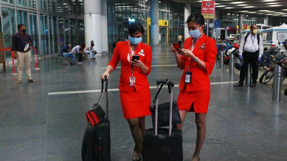 AirAsia Airlines Air hostess wearing protective mask watch on his smartphone at the Netaji Subhas Chandra Bose International Airport on June 04, 2020 in Kolkata, India.