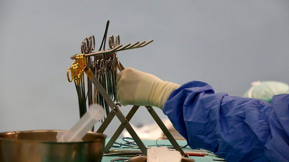 A doctor reaching for surgical instruments