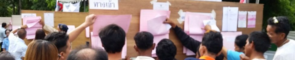 Thai voters check their names on registration lists at a polling station in Bangkok
