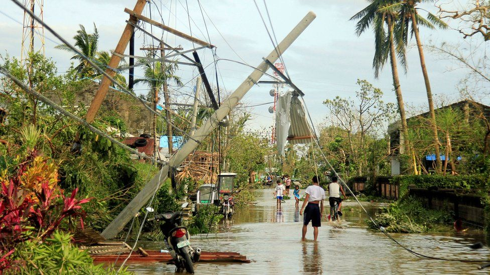 Residents walk past partially toppled electric posts after Typhoon Nock Ten hit Malinao, Albay in central Philippines