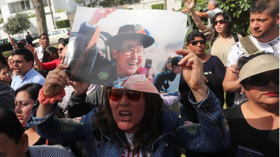 A supporter holds a picture of former President Alberto Fujimori as they wait outside his residence, after a judge annulled a presidential pardon and ordered his immediate capture and return to prison, in Lima, Peru October 3, 2018