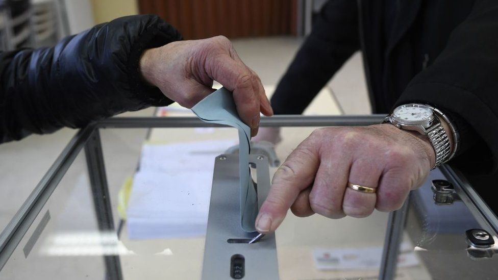 A woman casts her ballot at a polling station