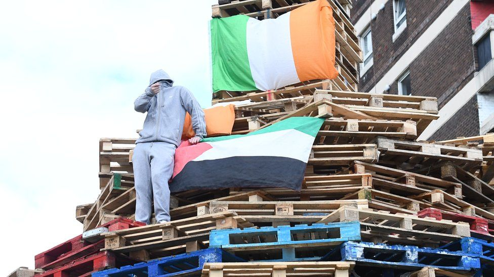 Youth on top of New Lodge bonfire