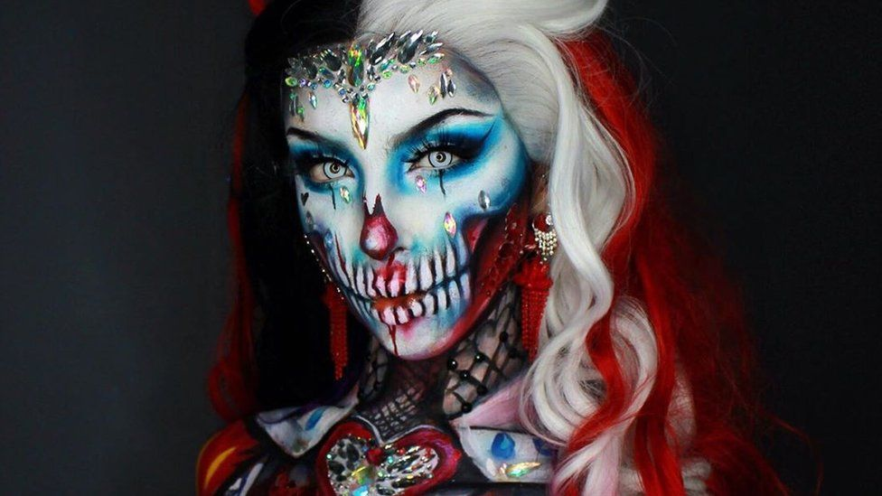 Body painter Ellie pints herself as a bejewelled queen of hearts skull with a red and white wig a crown and a jewelled corset painted to her torso