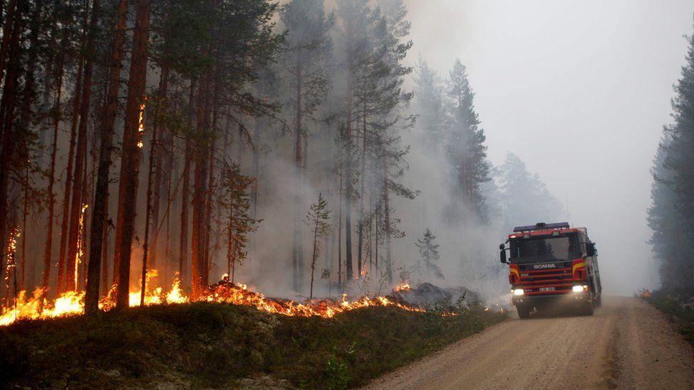 A fire vehicle is seen as fire burns in Karbole, Sweden, on July 15, 2018.
