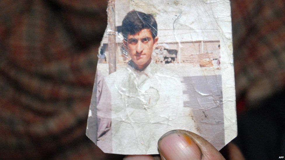 One of Shafqat Hussain's parents holds a photo of him