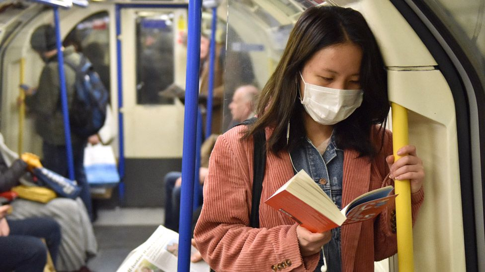 Woman reading a book on the London Underground`