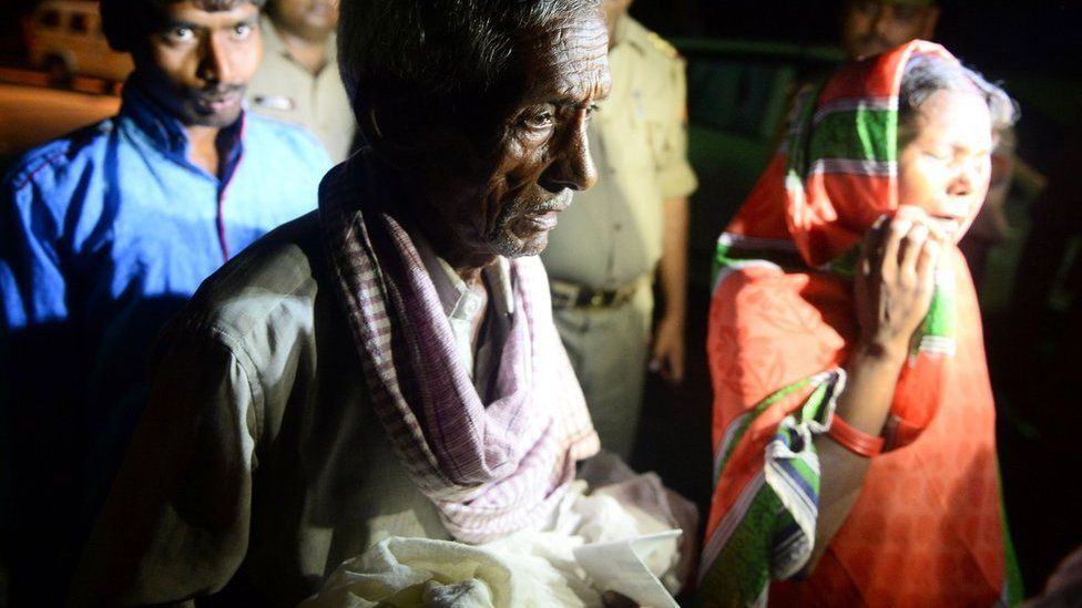 A relative carries a dead child out of the hospital