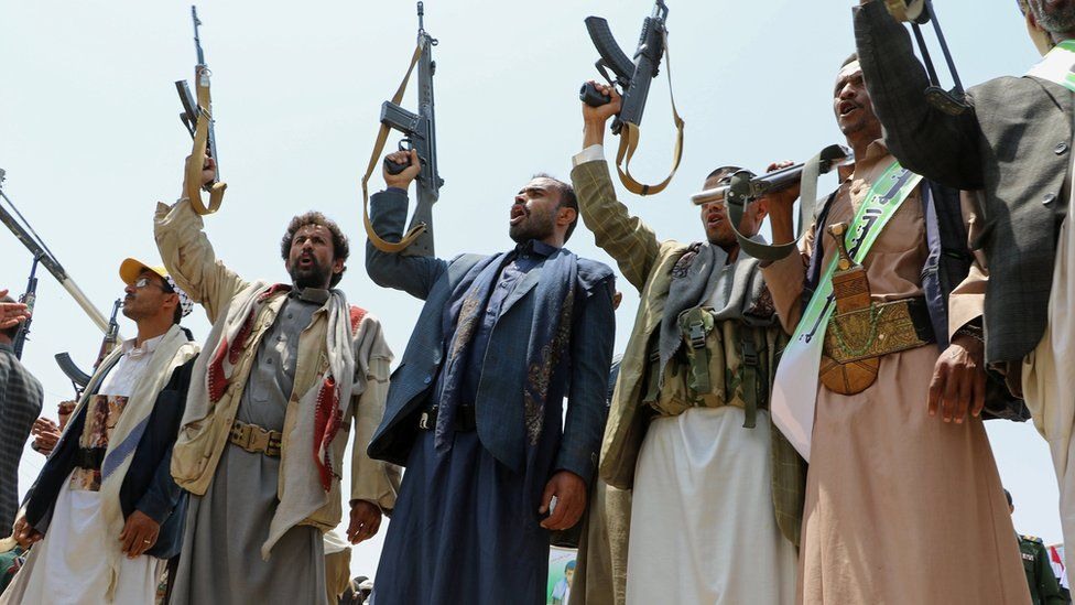 Mourners hold up their rifles as they attend a mass funeral in Saada, Yemen on 13 August 2018.