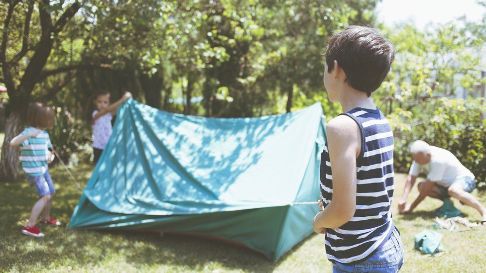 Stock image of children building a makeshift tent