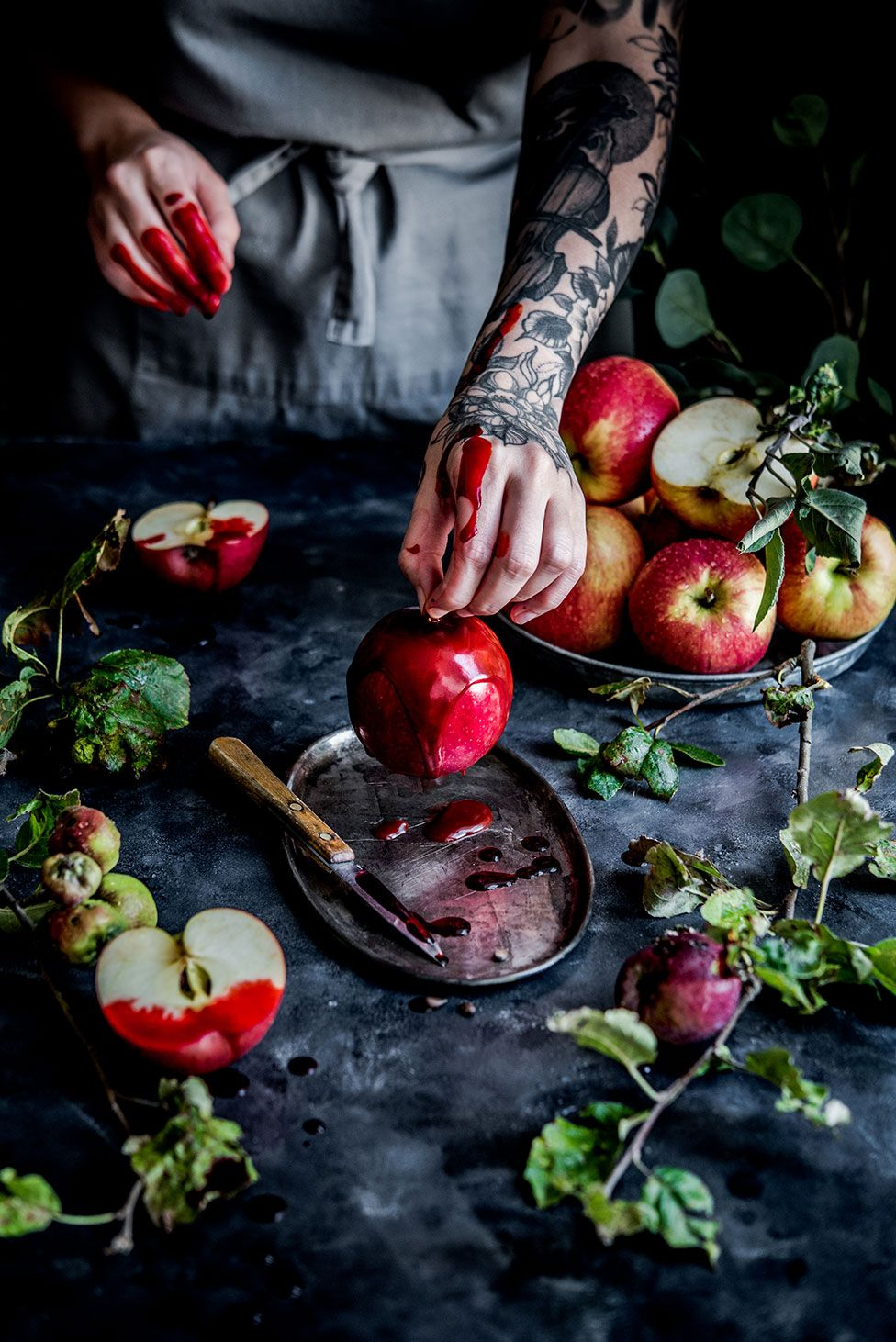 An arm with tattoos on holds an apple that has been dipped in syrup