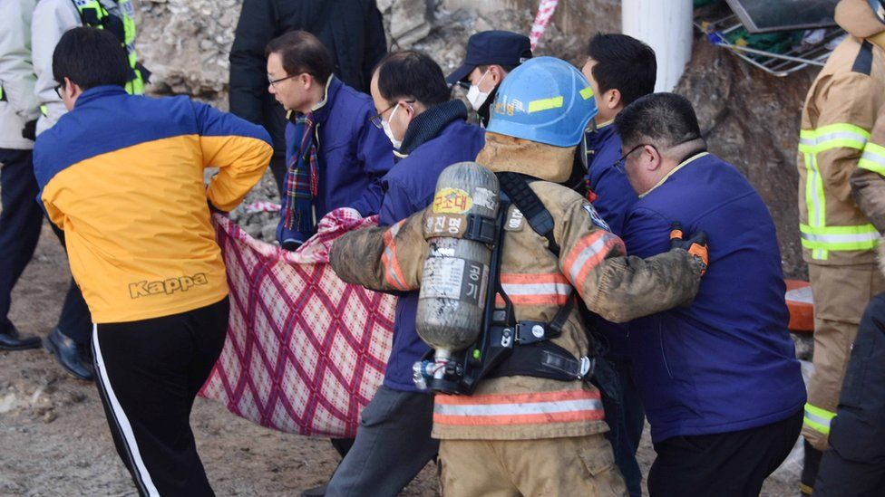 A handout photo made available by Kyongnamdomin Ilbo shows South Korean firefighters carrying a victim after a fire at a hospital in Miryang, South Korea, 26 January 2018