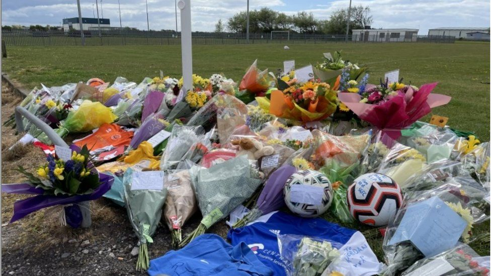 Flowers and football boots at the scene