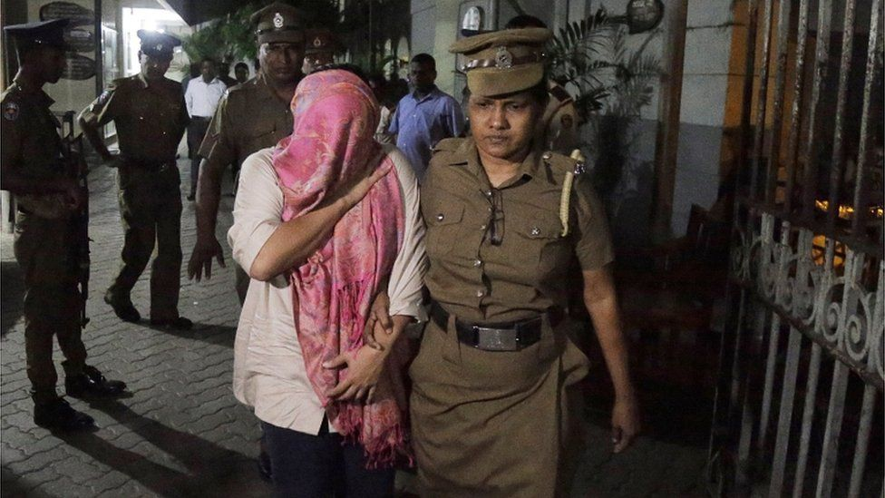 The employee of the Swiss embassy in Sri Lanka (head covered) is escorted by a police officer in Colombo on 16 December 2019