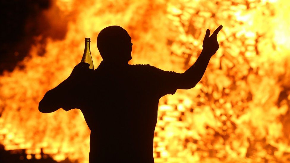 A man dances near a bonfire at Hopewell Square in Belfast's Shankill area