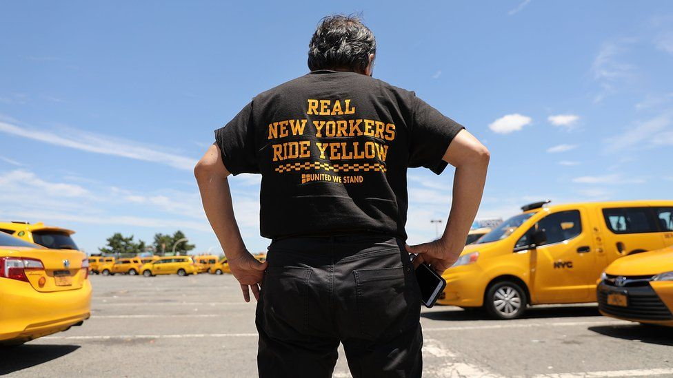 "A taxi driver stands in front of Yellow cabs at JFK wearing a shirt that says ""real New Yorkers ride yellow"""