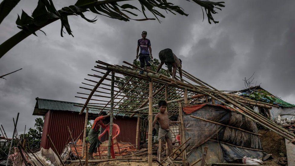 Men rebuilding a hut