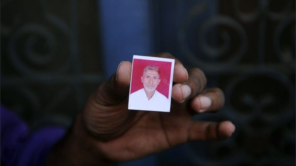 In this photograph taken on September 29, 2015, a relative holds a photograph of slain Indian villager Mohammad Akhlaq at his home in the village of Bisada, some 35 kilometres (22 miles) north-east of New Delhi,