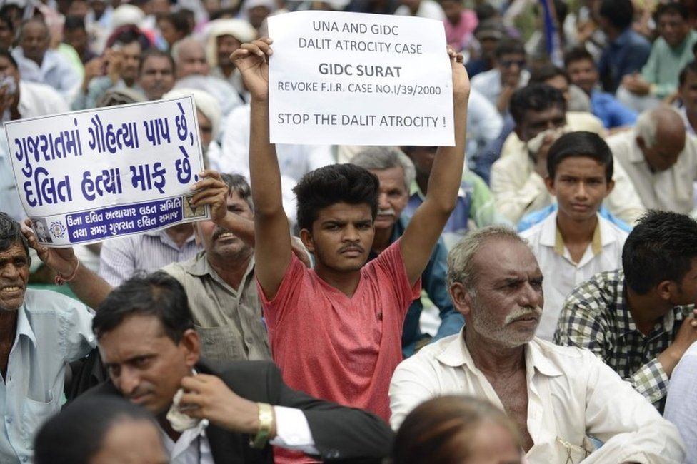 """An Indian member of the Dalit caste community holds a placard saying """"In Gujarat, Cow Slaughter is a Sin while Killing Dalits is pardonable"""" (L) as he participates in a protest rally against an attack on Dalit caste members in the Gujarat town of Una, in Ahmedabad on July 31, 2016."""