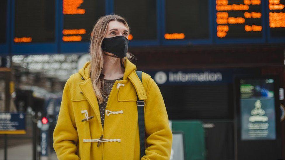 A woman waits at a train station