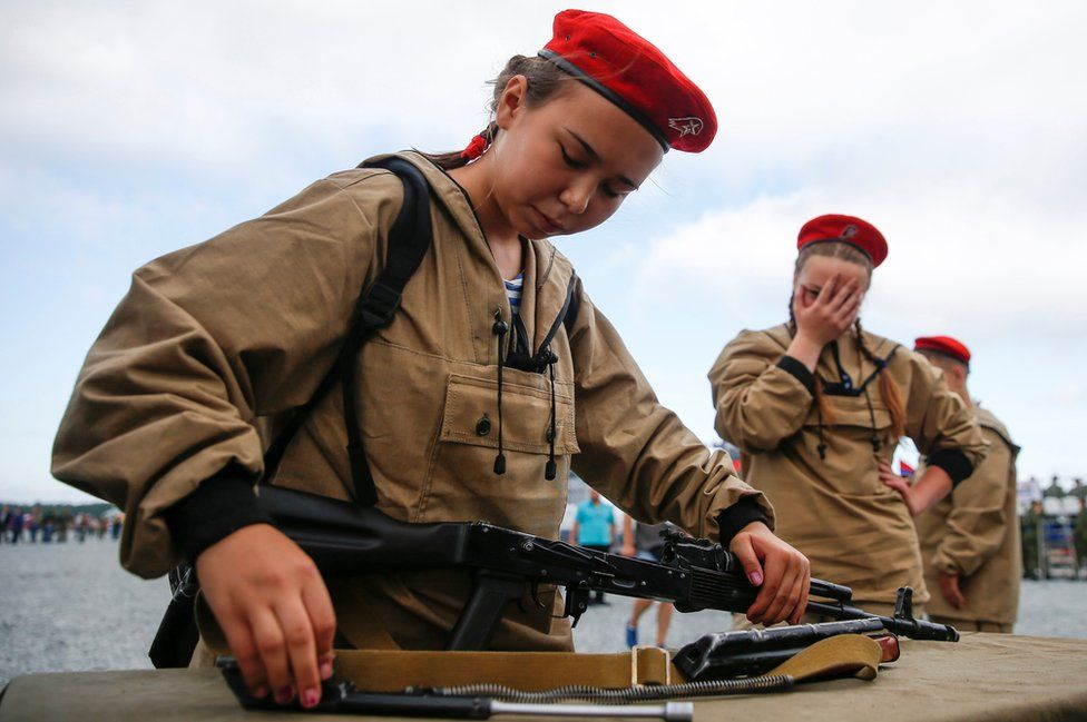 A girl in army wear concentrates on assembling a gun at the 2017 International Army Games.