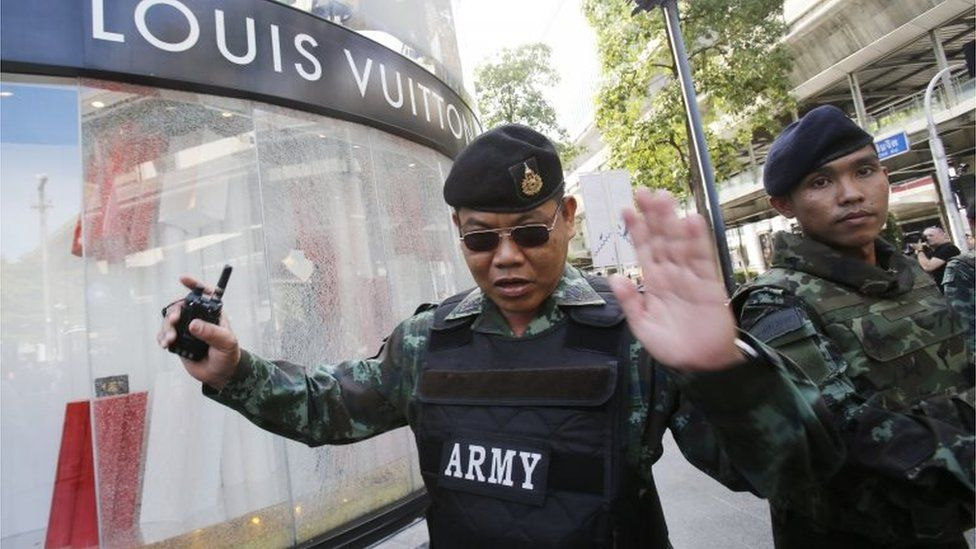 Soldiers move onlookers back from the shattered windows of a Louis Vuitton shop at Gaysorn shopping plaza across from the Erawan Shrine at Rajprasong intersection in Bangkok, Thailand, Tuesday, Aug. 18, 2015, as investigations continue the morning after an explosion.